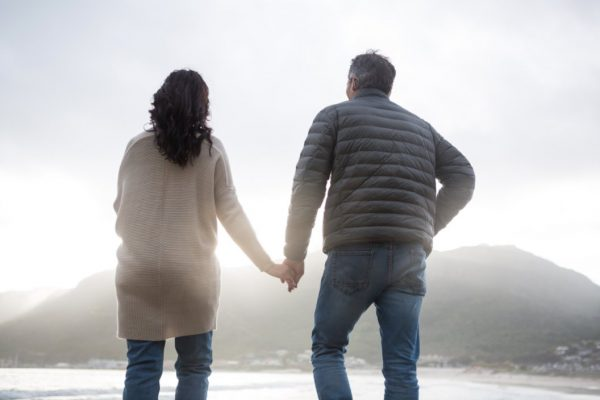 Rear view of couple holding hands on beach during winter